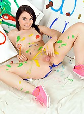 Pretty artistic teenager painting her beautiful naked body
